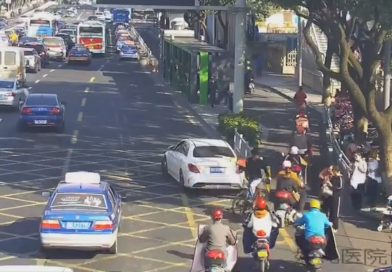 Cyclist With Toy Gun Rides Backwards In Busy Traffic